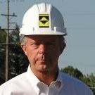 Leonard J. Theisen, the founder of Site Development, Inc., wearing a white button up shirt and a Site Development, Inc. hardhat.